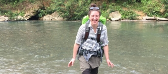 Lizzie Crouch wading through river with backpack